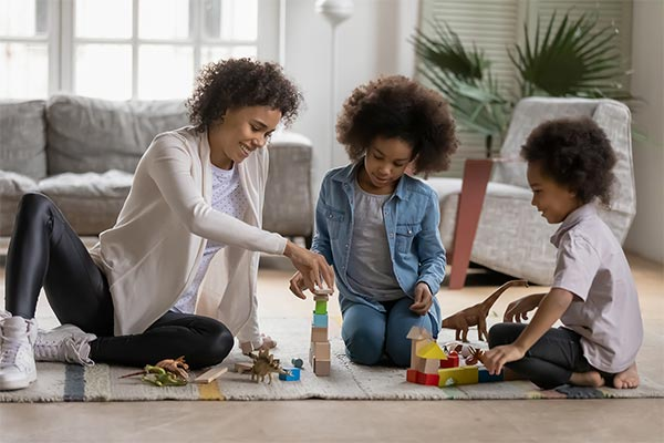 Mother And Children Play With Blocks In Living Room