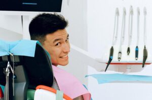 Smiling Patient Sitting in Dental Exam Chair